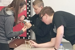 Three Junior High students work on making their bridge sturdy.